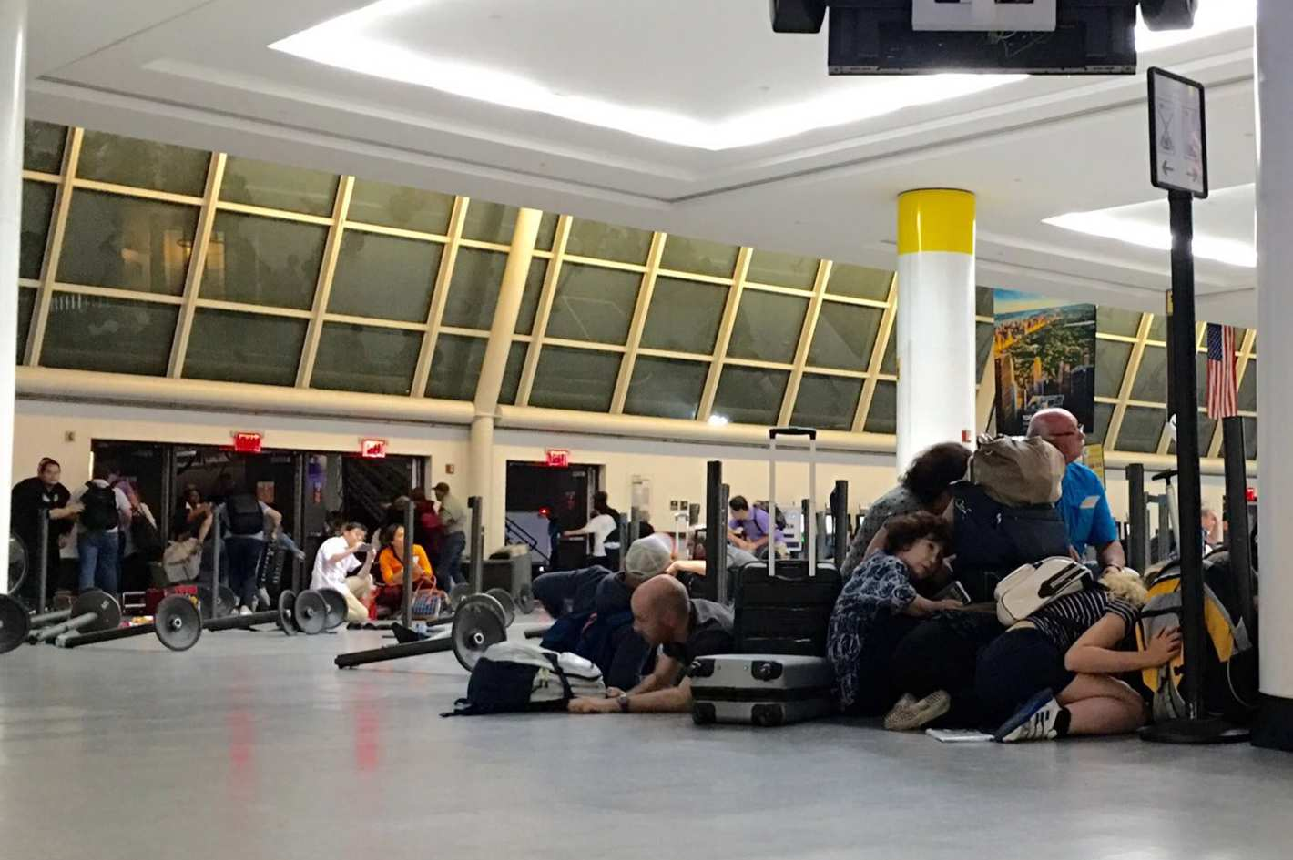 Hundreds of passengers take cover behind their baggage.
